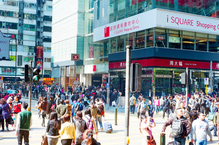 visitors area: HONG KONG - JAN 19, 2013: People crosing the street in Hong Kong. With a land mass of 1,104 km and population of 7 million people, Hong Kong is one of the most densely populated areas in the world