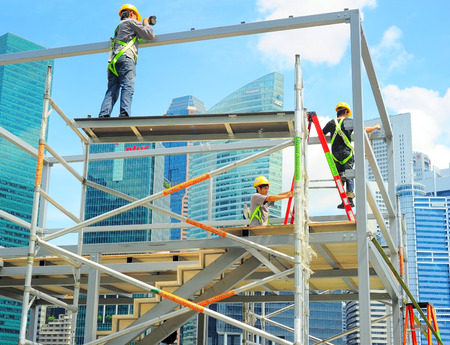 SINGAPORE - MAY 09, 2013: Workers at construction site in front of Singapore downtown in Singapore. Construction industry is expected to pull in some $30 billion this year