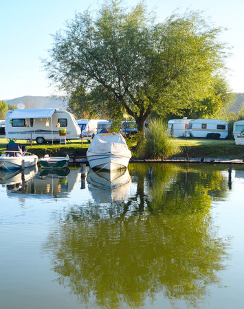 Campsite on a lake with caravans and boats