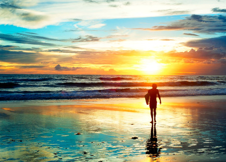夕日の光のビーチを歩いてサーファー。バリ島、インドネシア 写真素材
