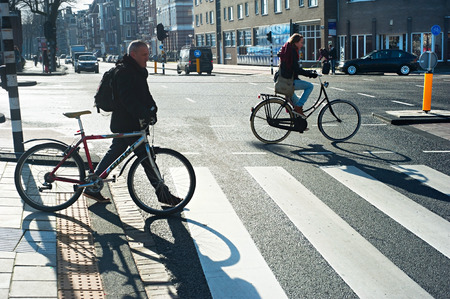AMSTERDAM, NETHERLANDS - FEB 26, 2014: Unidentified people crossing the street by bicycle. It is one of the most cycle-friendly cities in the world. 58% of the citizens uses daily a bicycle.