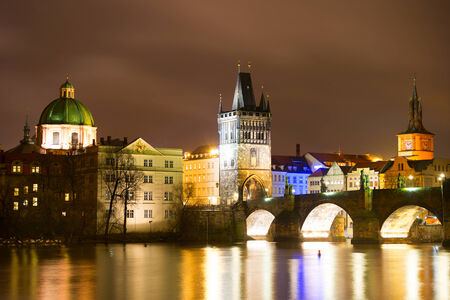 Night view of Charles bridge and Church of St. Francis in Prague photo