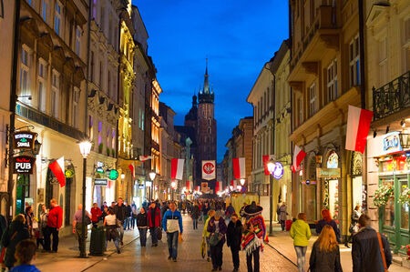 polska monument: KRAKOW, POLAND - NOV 10, 2014: People walking on Old Town street of Krakow. Krakow Old Town is one of the most famous old districts in Poland today and was the center of Polands political life from 1038