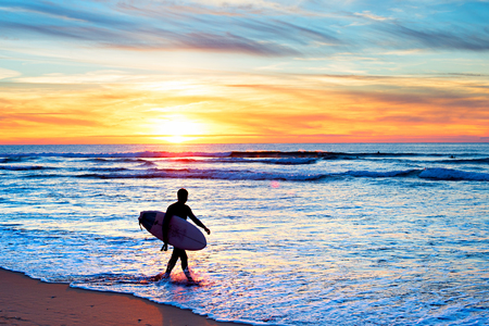 Surfer with surfboard walking on the beach at sunset