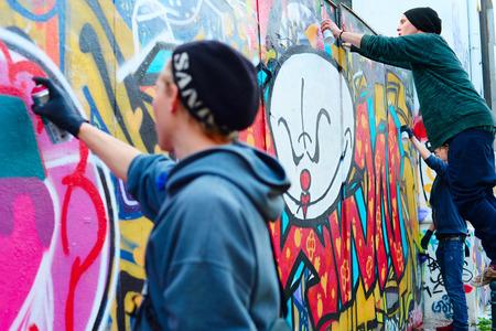 grafitis: LISBOA, Portugal - 23 de diciembre 2014: Muchachos que pintan graffiti en la pared en Lisbon.Along con Londres, Berl�n, Nueva York y otros, Lisboa es una de las grandes ciudades del mundo para el graffiti y el arte urbano. Editorial