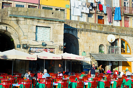 traditon: PORTO, PORTUGAL - JAN 12, 2015: Unidentified people at street restaurant on the embankment of Porto. Porto is one of the oldest European centres, and its historical core was proclaimed a World Heritage Site by UNESCO in 1996