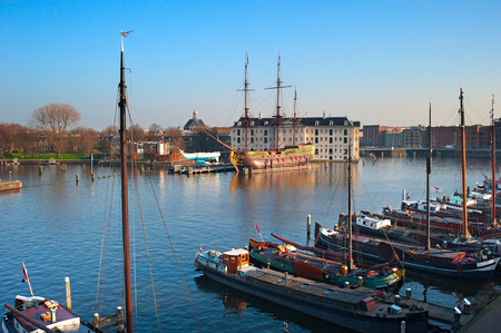 amstel river: Row of houseboats on the Amstel river in Amsterdam, Netherlands. National Maritime Museum on the background Stock Photo