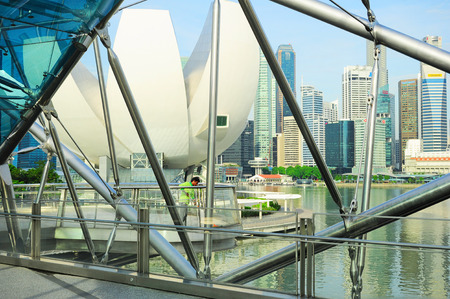 tonnes: SINGAPORE - MAY 07, 2013: Worker cleaning the Helix bridge in front of Singapore downtown. The Helix is fabricated from 650 tonnes of Duplex Stainless Steel and 1000 tonnes of carbon steel.