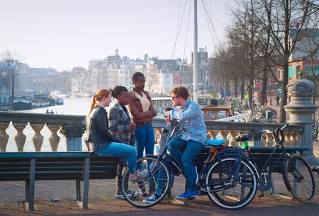 AMSTERDAM, NEDERLAND - 10 maart 2104: Multiculturele vrienden in gesprek over de straat van Amsterdam. In totaal 177 verschillende nationaliteiten woonachtig in Amsterdam, waardoor het de meest multiculturele stad ter wereld.