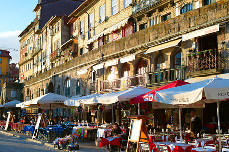 proclaimed: PORTO, PORTUGAL - JAN 12, 2015: Unidentified people at street restaurant on the embankment of Porto. Porto historical core was proclaimed a World Heritage Site by UNESCO in 1996