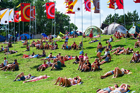 open air: BUDAPEST, HUNGARY - AUGUST 13, 2014: Visitors of Sziget music festival relaxing in the day. Sziget is one of biggest festivals in Europe