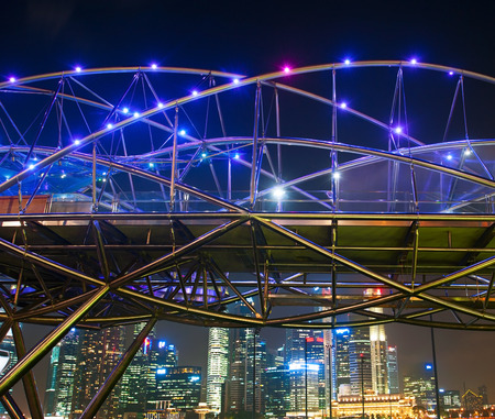 tonnes: SINGAPORE - MARCH 06, 2013: The Helix Bridge at night  in Singapore. The Helix is fabricated from 650 tonnes of Duplex Stainless Steel and 1000 tonnes of carbon steel.