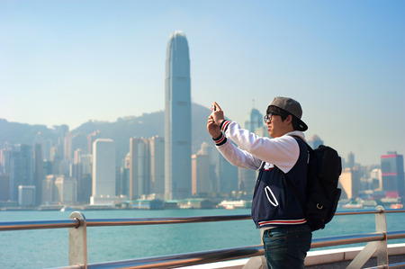 tourism industry: HONG KONG - JAN 14, 2013: Unidentified man taking a picture of Hong Kong skyline by his phone. The tourism industry  an important part of the economy of Hong Kong
