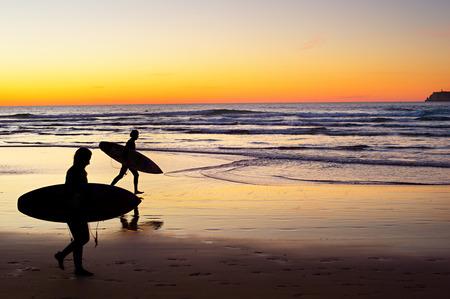 Deux surfeur courir sur la plage au coucher du soleil. Le Portugal a l'une des meilleures scènes de surf en Europe