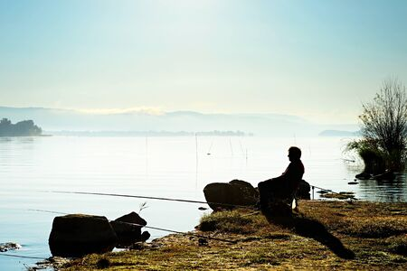 Silhouette of a fisherman on the lake at sunrise photo