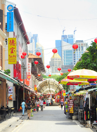 settling: SINGAPORE - MARCH 5, 2013 : Shoppers walking through Chinatown street in Singapore. The city states ethnic Chinese began settling in Chinatown circa 1820s. Editorial