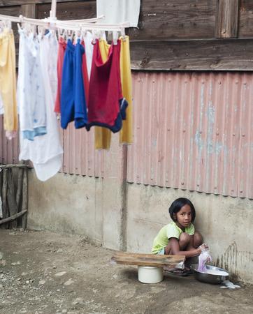 lavando ropa: AGADA, FILIPINAS - 23 de marzo de 2012: chicas lavando ropa en el pequeño pueblo de Filipinas. Alrededor del 12 por ciento de los niños de Filipinas entre las edades de cinco y 14 se ven obligados a trabajar. Editorial