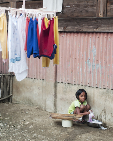 traditional clothes: AGADA, PHILIPPINES - MARCH 23, 2012: Girl washing clothes in the small village in Philippines. About 12 per cent of Philippines children between the ages of five and 14 are forced to work. Editorial