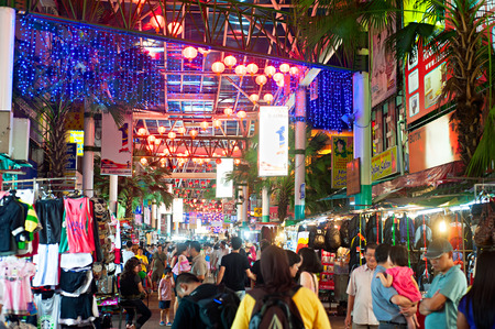 KUALA LUMPUR, MALAYSIA - MARCH 30, 2012: People on Petaling Street  in Kuala Lumpur. The street is a long market which specialises in counterfeit clothes, watches and shoes. Famous tourist attraction
