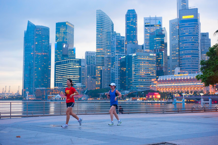 recognized: SINGAPORE - MAY 06, 2012: Unidentified people runnig in front of Singapore downtown in Singapore. Singapore has been recognized as one of the best cities for runners in Asia.