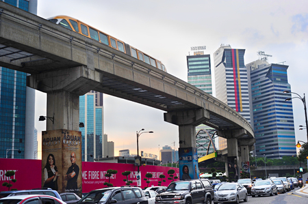 kuala: KUALA LUMPUR, MALAYSIA - MARCH 16, 2011: Traffic jam during rush hour and monorail train on elevated rail section in Kuala Lumpur. Kuala Lumpur is the capital of Malaysia.