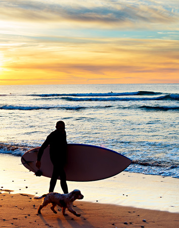 unrecognizable: Silhouette of a surfer with a dog at sunset on the beach. Portugal