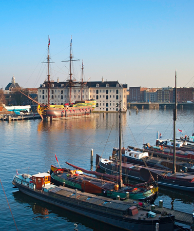amstel river: Houseboats on the Amstel river in Amsterdam, Netherlands. National Maritime Museum on the background