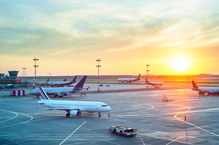 flight: Airport with many airplanes at beautiful sunset Editorial