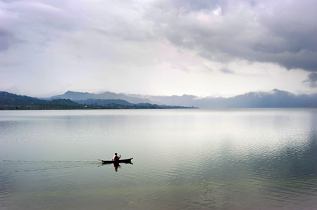 one man: Lonely fisherman on a lake Batur. Bali island. Indonesia