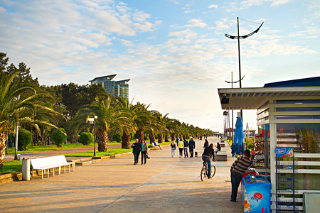 promenade: BATUMI, GEORGIA - MAY 11, 2015: People walking on embankment at sunset in Batumi. Batumi - city on the Black Sea coast and capital of autonomous republic Adjara, Georgia.