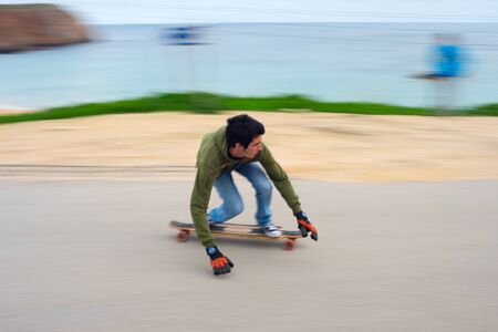 certain: SAGRES, PORTUGAL - DEC 27, 2014: Blured motion of teenagers on a longboard going down the hill. Longboard is a type of sports equipment somewhat similar to a skateboard, but in a certain way longer. Editorial