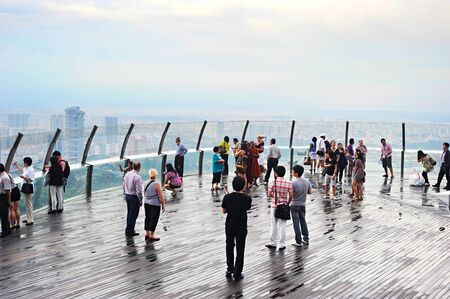 point of view: SINGAPORE - MAY 04, 2015: People at view point on top of Marina Bay Sands Hotel. It is billed as the worlds most expensive standalone casino property at S$8 billion
