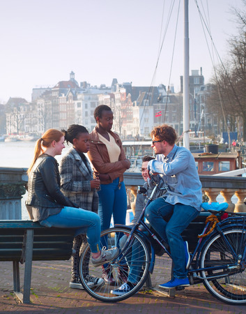 holland: AMSTERDAM, NETHERLANDS - MARCH 10, 2104: Multicultural friends in conversation on the street of Amsterdam. Total of 177 different nationalities are residing in Amsterdam, making it the most multi-cultural city in the world.