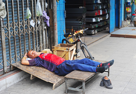 industry park: BANGKOK, THAILAND - MARCH 26, 2011: Unidentified man sleeping on the street in tha day. Bangkok is a capital of Thailand