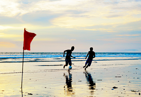 indonesian flag: People playing football on the beach at sunset. Bali, Indonesia