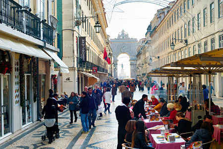LISBON, PORTUGAL - DEC 24, 2014: People on Augusta street in the day.  Augusta Street with the Triumphal Arch - is the famous tourist attraction in Lisbon. Editorial