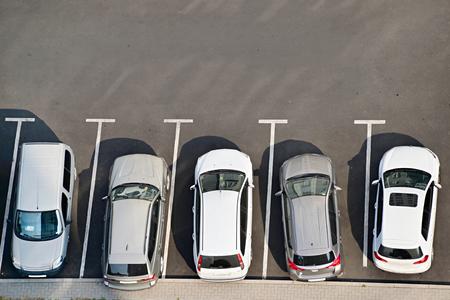 Bovenaanzicht van een parkeerplaats vol met auto's.