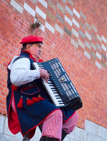 伝統: クラクフ、ポーランド - 2014 年 11 月 11 日: ストリートミュージ シャンをクラクフの通りで遊んでポーランドの伝統的な衣装で着ていた。