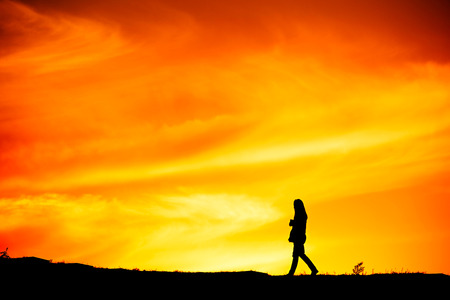 lonely woman: SIlhouette of a lonely woman walking at sunset on a hill Stock Photo
