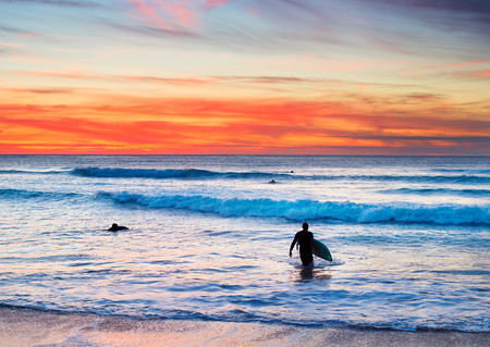 male surfer: Surfer with surfboard walking out of the ocean at sunset