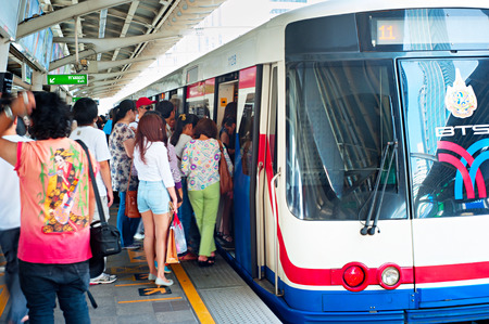 BANGKOK - MARCH 17, 2013: People board a BTS Skytrain at a city centre station. The Thai capitals BTS rail public transport system serves 600,000 passengers daily. Editorial