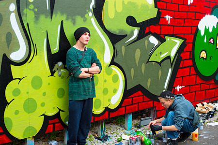 painting art: LISBON, PORTUGAL - DECEMBER 23, 2014: Boys painting graffiti on the wall in Lisbon.Along with London, Berlin, New York and others, Lisbon is one of the worlds great cities for graffiti and street art Editorial