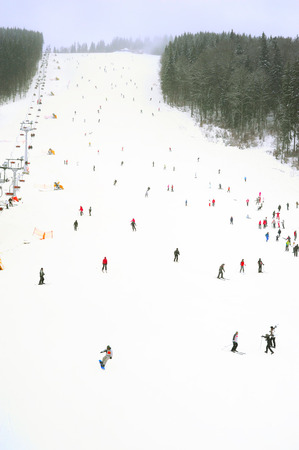 slopes: Skiers and snowboarders on a slope at sky resort during the heavy snowfall
