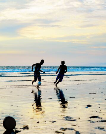 adult indonesia: People playing football on the beach at sunset. Bali, Indonesia