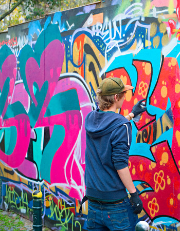 one teenager: LISBON, PORTUGAL - DECEMBER 23, 2014: Teenager painting graffiti on the wall in Lisbon.Along with London, Berlin, New York and others, Lisbon is one of the worlds great cities for graffiti and street art