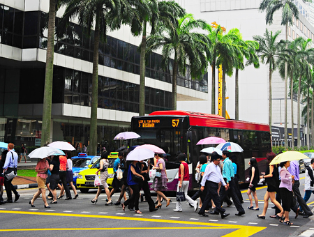 SINGAPORE - MARCH 06, 2013: People crossing the street in the rain in Singapore Downtown Core. There are more than 7,000 multinational corporations from US States, Japan and Europe in Singapore