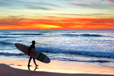 portugal: Surfer on the ocean beach at colorful sunset. Portugal