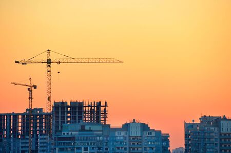 worksite: Cranes at construction site in the colorful sunset