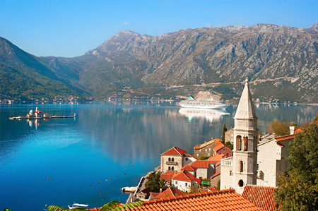 View on Perast town with Church Our Lady of the rocks and cruise liner. Montenegro