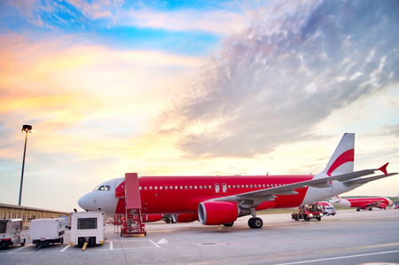 Airplane at airport in the colorful sunrise.